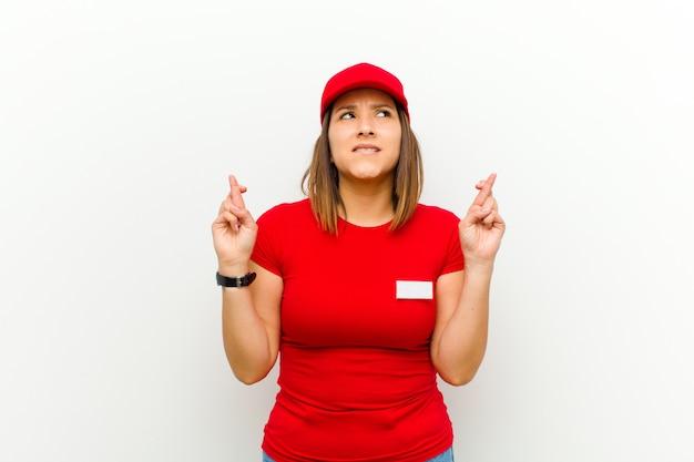 Lieferungsfrau, die besorgt finger kreuzt und auf gutes glück mit einem besorgten blick gegen weißen hintergrund hofft