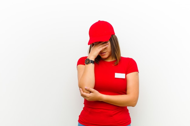 Lieferungsfrau, die betont, beschämt oder, mit kopfschmerzen aufgeregt schaut und gesicht mit der hand bedeckt