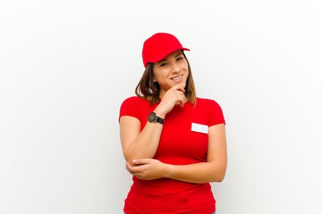 Lieferungsfrau, die glücklich schaut und mit der hand auf dem kinn sich wundert oder eine frage stellt, die wahlen vergleicht