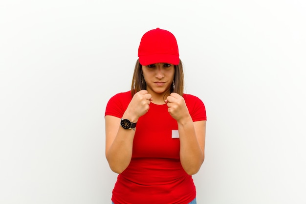 Lieferungsfrau, die überzeugt, verärgert, stark und aggressiv, mit den fäusten bereit schaut, in verpackenstellungsweiß zu kämpfen