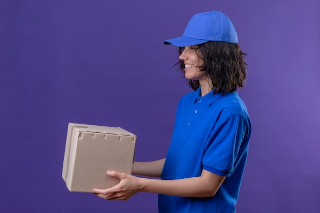 Lieferungsmädchen in der blauen uniform und in der kappe, die seitlich stehen, geben boxpaket zu einem kunden, der freundlich lächelt