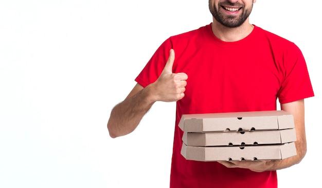 Lieferungspizzajunge, der kästen und daumen herauf mittleren schuss hält