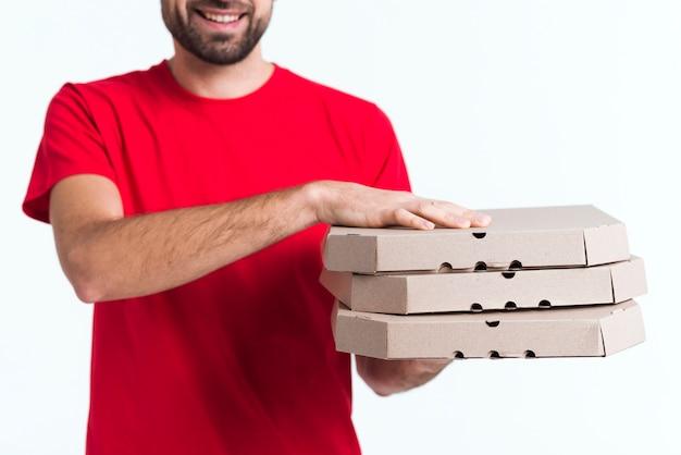 Lieferungspizzajunge, der mittleren schuss der kästen hält