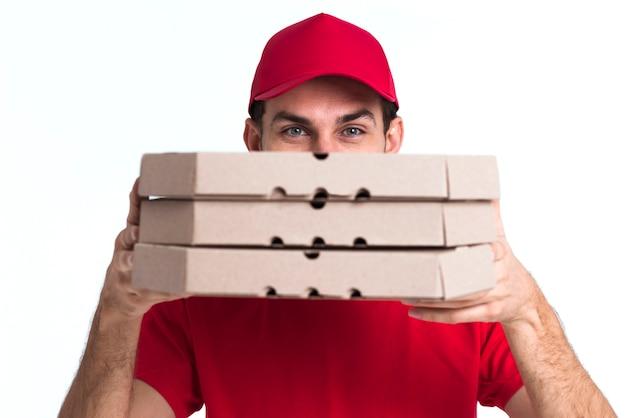 Lieferungspizzajunge, der sein gesicht mit kästen bedeckt