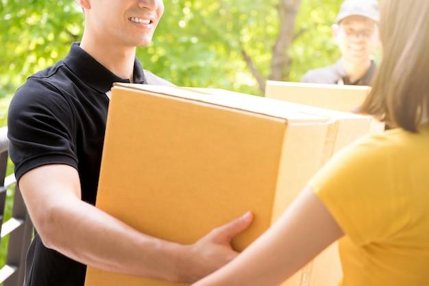 Lieferungsteam, das pakete an eine frau liefert