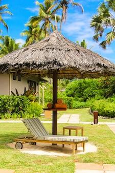 Liege unter einem regenschirm im hotelpool auf den seychellen