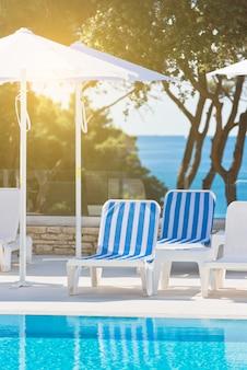 Liegen und sonnenschirme am pool an einem sonnigen tag