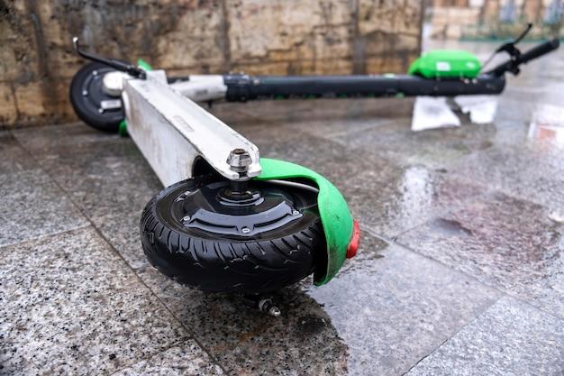 Liegender elektroroller zum teilen auf dem nassen boden bei bewölktem wetter in bukarest, rumänien