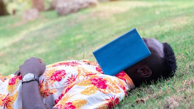 Liegender schlaf des afrikanischen reisendmannes auf dem gras mit geöffnetem buch