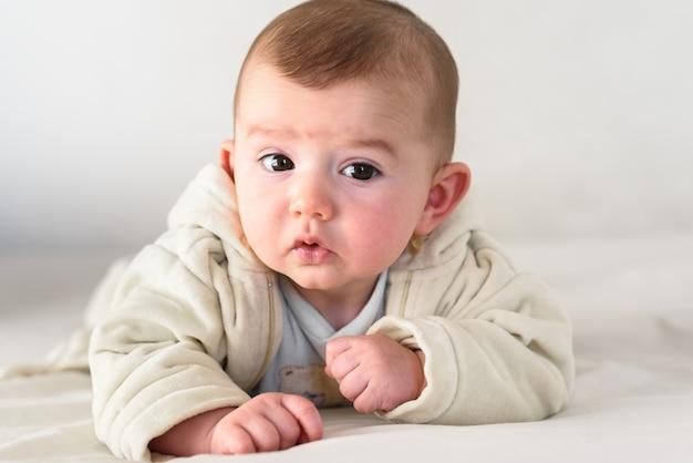 Liegendes gesicht des schönen und süßen neugeborenen babys unten auf dem bett, das seinen kopf anhebt, um neugierig die kamera zu betrachten.