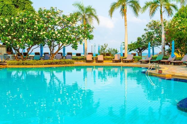 Liegepool und sonnenschirm rund um den swimmingpool mit kokospalme - urlaub und urlaubskonzept