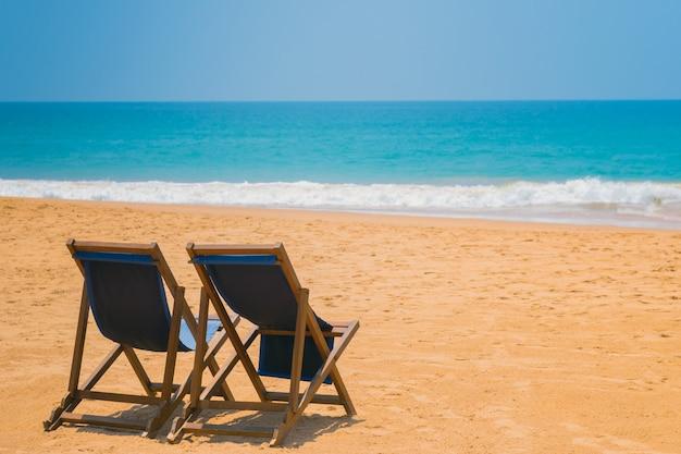 Liegestühle am sandstrand des ozeans.
