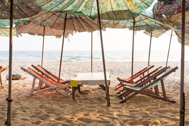 Liegestühle im urlaubsgebiet. strandliegen auf verlassenem küstenmeer.
