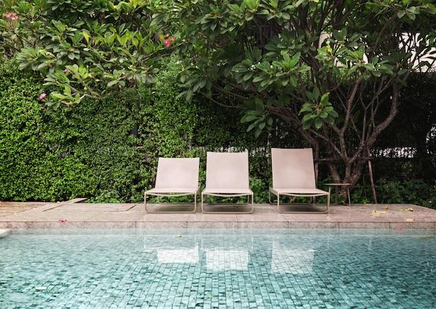 Liegestühle in der nähe von schwimmbad