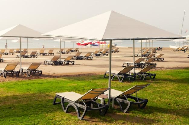 Liegestühle mit sonnenschirmen am strand, perspektive. hotel, sommerferien