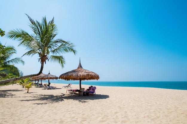 Liegestühle, sonnenschirm und palmen am sandstrand in der nähe von meer. insel in phuket, thailand.
