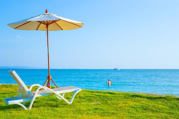 Liegestühle und sonnenschirme stehen auf der liegewiese am strand.