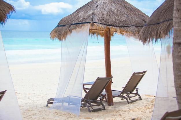 Liegestühle unter strohgedeckten sonnenschirmen auf tropischem strand