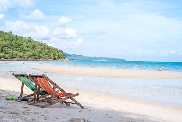 Liegestuhl am sandstrand mit blauem meer, bergen und klarem himmel