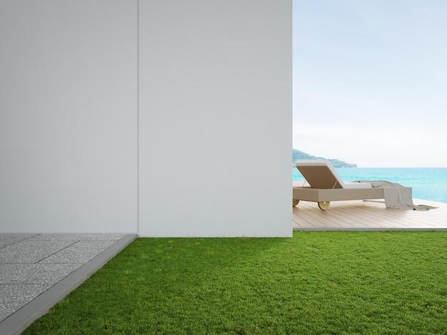 Liegestuhl auf der terrasse in der nähe von pool und garten im modernen strandhaus