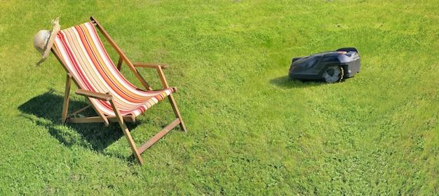 Liegestuhl auf grünem gras in einem garten in panoramagröße
