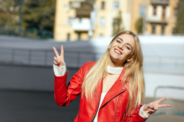 Lifestyle-aufnahme: entzückende glückliche frau in roter lederjacke mit friedenshandzeichen. platz für text