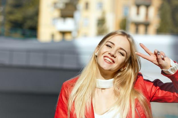 Lifestyle-aufnahme: fröhliches glückliches modell in roter lederjacke mit friedenshandzeichen. platz für text