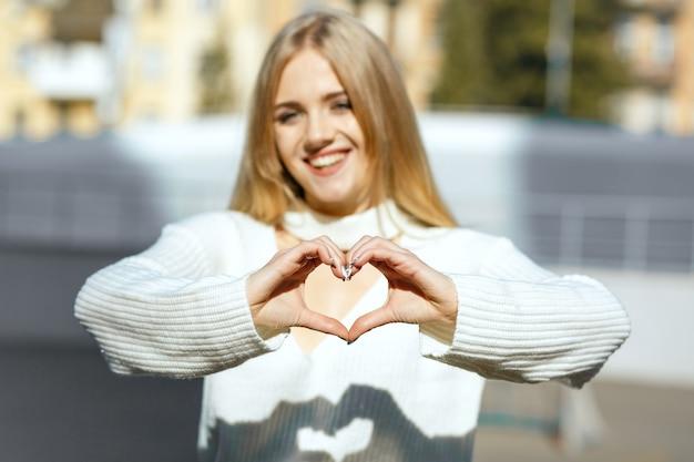 Lifestyle-aufnahme: glückliches blondes mädchen in weißem strickpullover, das mit ihren händen ein herzsymbol macht