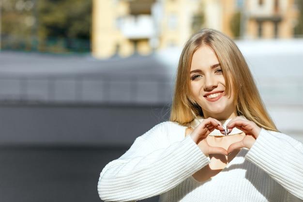 Lifestyle-aufnahme: wunderschönes blondes mädchen in weißem strickpullover, das mit ihren händen ein herzsymbol bildet. platz für text