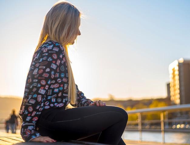 Lifestyle, eine hübsche blondine, die die stadt mit einem blauen hemd genießt