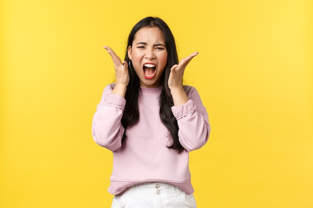 Lifestyle, emotionen und werbekonzept. wütende verzweifelte asiatische frau, die hasserfüllt und empört schreit, sich von schlechten nachrichten überwältigt fühlt, auf eine schreckliche situation reagiert, sich wütend fühlt.