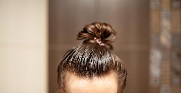 Lifestyle-frau malt hennagraues haar, haarfärbe-selbstpflege. haarpflege zu hause. die frau trug eine maske oder einen balsam auf ihr haar auf.