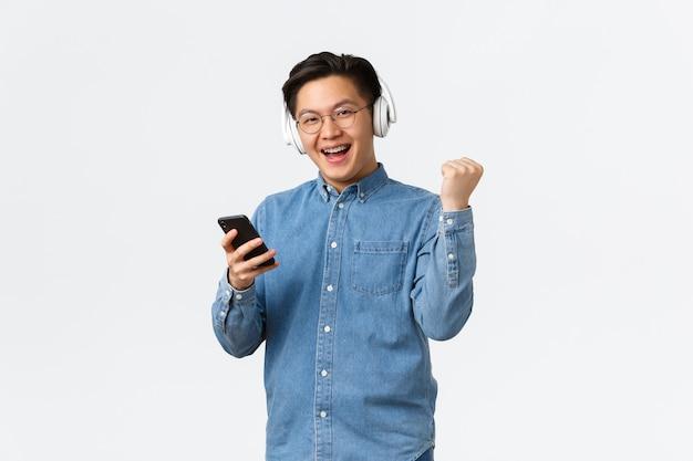 Lifestyle-, freizeit- und technologiekonzept. gewinnen zufriedener asiatischer mann in gläsern, musik hörend