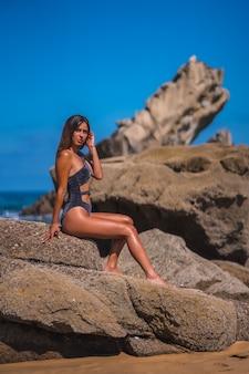 Lifestyle, kaukasische brünette in einem luxuriösen schwarzen badeanzug mit glitzern, die den sommer auf see genießen.
