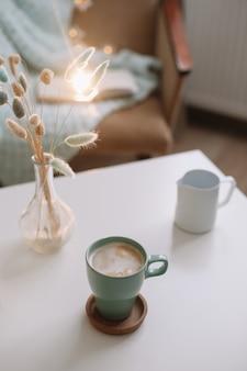 Lifestyle-komposition mit tasse kaffee und einer vase mit blumen auf einem couchtisch.