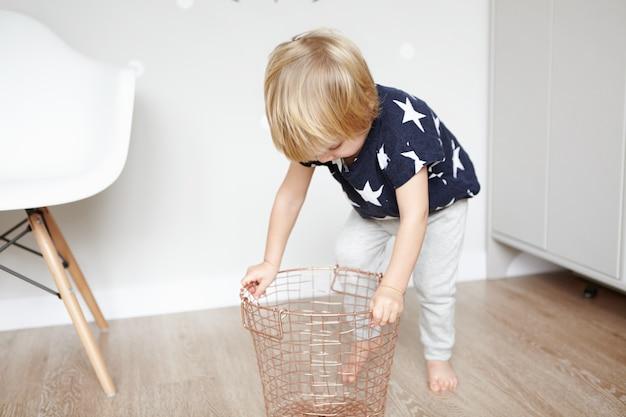 Lifestyle-konzept. gemütlicher süßer schuss des niedlichen zweijährigen kleinkindes, das mit dekorativem metallkorb im schlafzimmer spielt.