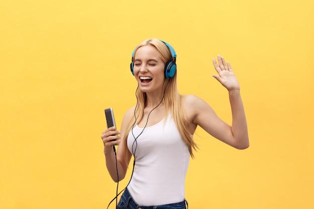 Lifestyle-konzept: porträt einer freudigen frau im weißen t-shirt und beim hören musik