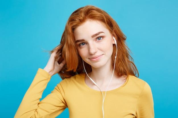 Lifestyle-konzept - porträt von fröhlich glücklich ingwer rote haare mädchen genießen musik hören mit kopfhörer freudig lächelnd kamera. isoliert auf blauem pastellhintergrund. platz kopieren