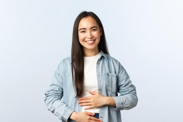 Lifestyle, menschen emotionen und schönheitskonzept. erfreut lächelnde asiatische frau, die sich den bauch reibt, nach dem essen voll ist, zufriedenes gefühl im magen vom trinken von joghurt