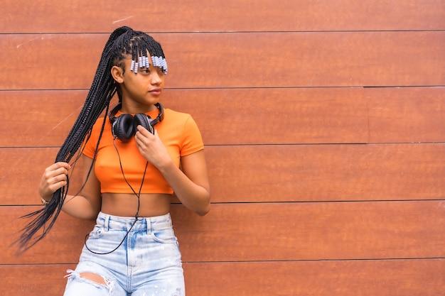 Lifestyle mit einem jungen trap-tänzer in der stadt. schwarzes grindmädchen der afrikanischen ethnischen gruppe mit orangefarbenem t-shirt und cowboyhosen, mit kopfhörern auf einem hölzernen hintergrund