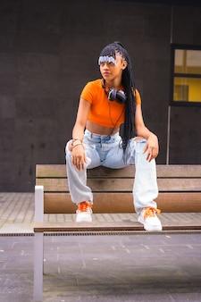 Lifestyle mit einem jungen trap-tänzer in der stadt. schwarzes grindmädchen der afrikanischen ethnischen gruppe mit orangefarbenem t-shirt und cowboyhosen, mit kopfhörern auf schwarzem hintergrund