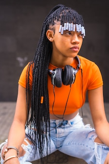Lifestyle mit einem jungen trap-tänzer mit zöpfen in der stadt. schwarzes race girl afrikanischer abstammung mit orange t-shirt und cowboyhose, vertikales foto