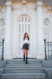 Lifestyle, modische pose einer jungen brünette mit schwarzem lederrock und hemd auf der treppe eines weißen hauses