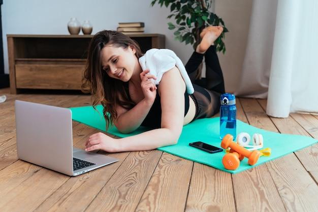 Lifestyle-momente einer jungen frau zu hause frau macht sportübungen im wohnzimmer