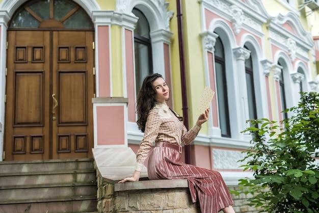 Lifestyle-porträt der hübschen dame in der nähe des hauses auf der stadtstraße