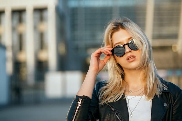 Lifestyle-porträt des jungen modischen mädchens mit spiegelsonnenbrille und lederjacke. platz für text