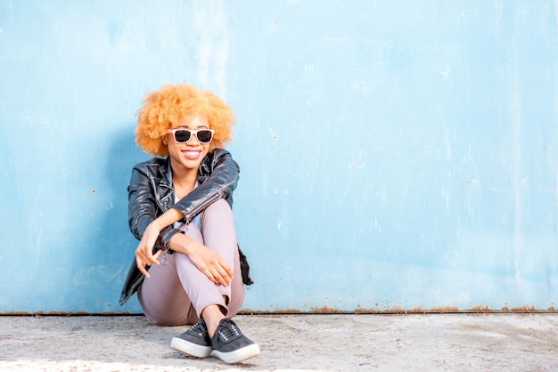 Lifestyle-porträt einer afrikanischen frau in lederjacke, die auf dem blauen wandhintergrund sitzt