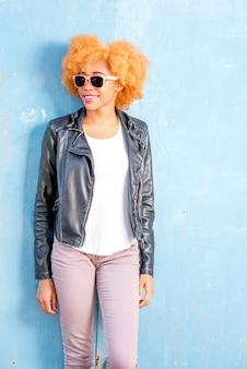 Lifestyle-porträt einer afrikanischen frau in lederjacke, die auf dem blauen wandhintergrund steht