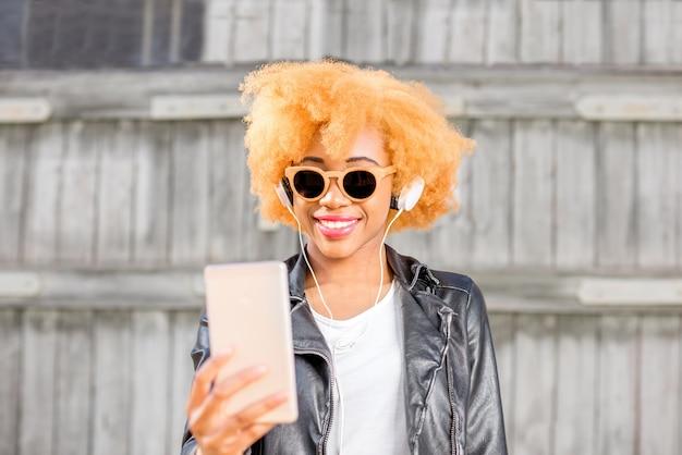 Lifestyle-porträt einer afrikanischen frau in lederjacke, die ein selfie-foto mit dem telefon macht, das auf dem holzwandhintergrund steht