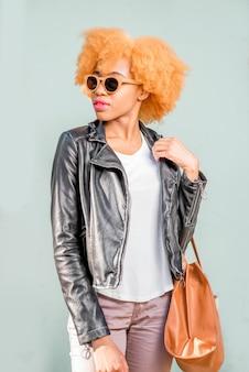 Lifestyle-porträt einer afrikanischen frau in lederjacke und sonnenbrille, die mit tasche auf dem grünen wandhintergrund steht